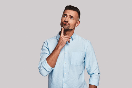 Looking for fresh ideas. Thoughtful young man keeping hand on chin and looking away while standing against grey background Stock Photo