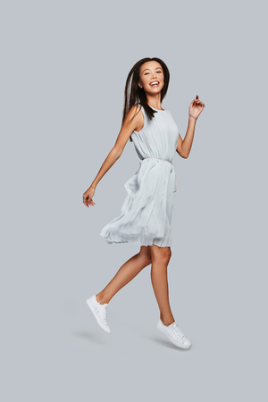 Beautiful perfection. Full length of beautiful young Asian woman smiling and looking at camera while standing against grey background