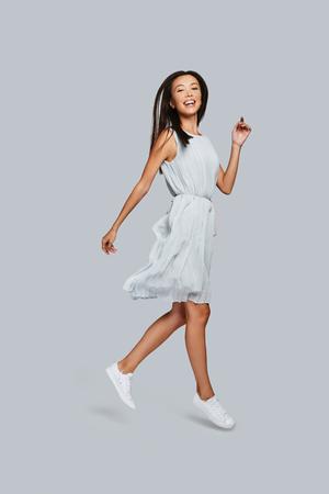 Schöne Perfektion. In voller Länge der schönen jungen asiatischen Frau, die beim Stehen gegen grauen Hintergrund lächelt und Kamera betrachtet Standard-Bild