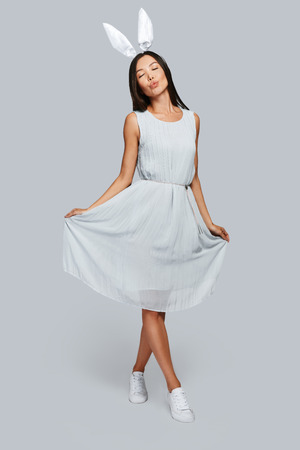 Effortless beauty. Full length of beautiful young Asian woman in bunny ears smiling while standing against grey background