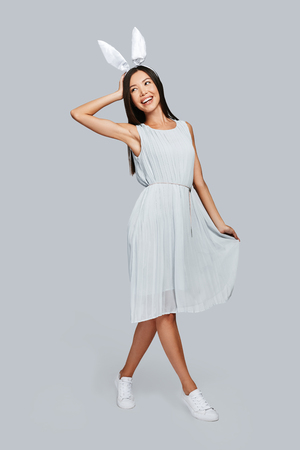 Carefree and happy. Full length of beautiful young Asian woman in bunny ears smiling while standing against grey background