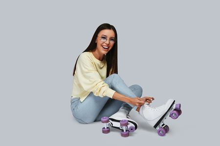Sincere fun. Beautiful young Asian woman tying roller skates and smiling while sitting against grey background