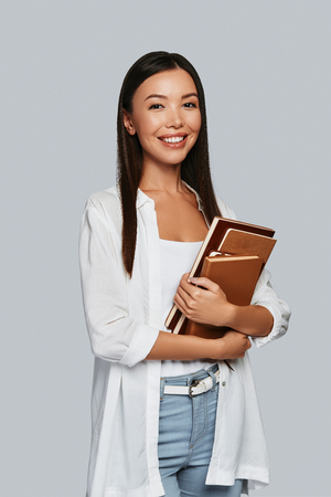 Intelligence. Beautiful young Asian woman carrying books and smiling while standing against grey background