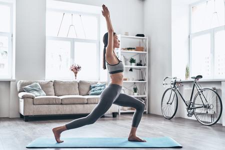 Rester en forme et en bonne santé. Belle jeune femme asiatique en vêtements de sport faisant du yoga tout en se relaxant à la maison
