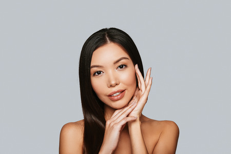 Perfect skin. Beautiful young Asian woman looking at camera and smiling while standing against grey background Imagens