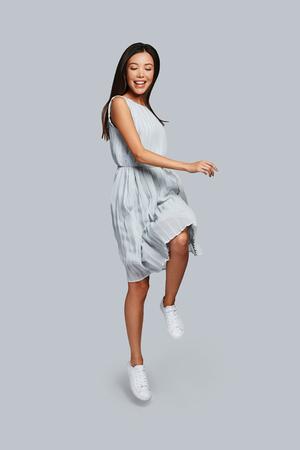 Speels. Volledige lengte van mooie jonge Aziatische vrouw die lacht terwijl ze tegen een grijze achtergrond springt Stockfoto