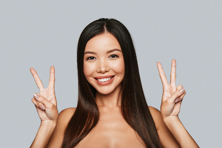 Victory. Beautiful young Asian woman gesturing and smiling while standing against grey background