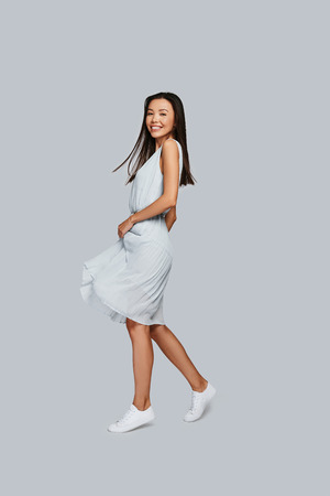 Pure feminine beauty. Full length of beautiful young Asian woman smiling and looking at camera while standing against grey background