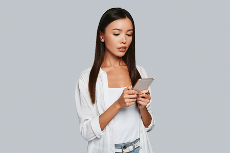 Chatting with friends. Beautiful young Asian woman using her smart phone while standing against grey background Stock Photo