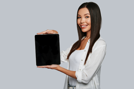 You should see this. Attractive young Asian woman pointing copy space on her digital tablet and smiling while standing against grey background Imagens - 112806173