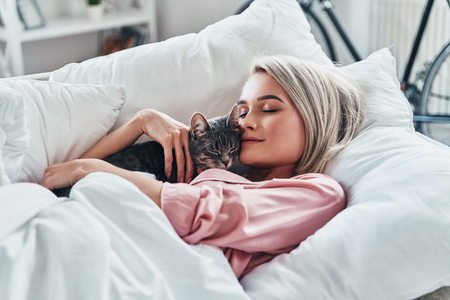 Loving her cat. Attractive young woman holding her cat and smiling while lying in bed at home
