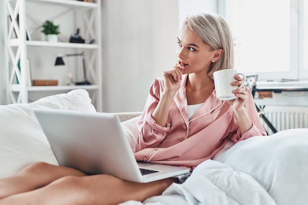 What if... Attractive young woman looking away and using laptop while sitting on bed at home Stock Photo