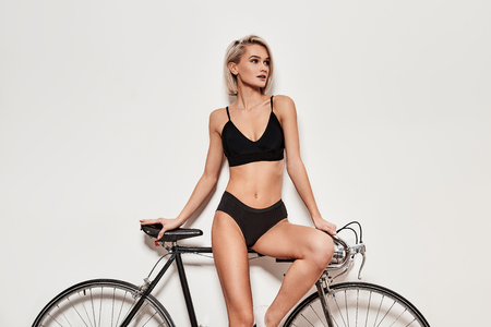 Looking amazing. Seductive young woman in lingerie leaning on the bicycle while standing against grey background