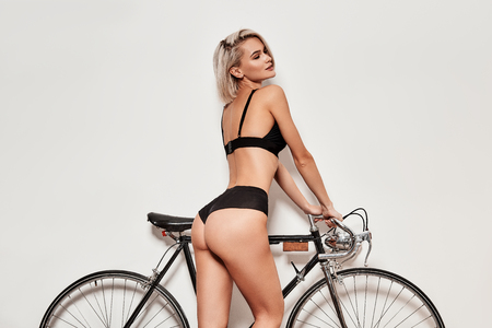 Perfect curves. Seductive young woman in lingerie smiling while posing near the bicycle against grey background
