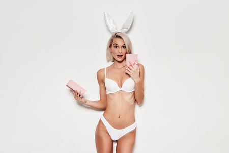 Best gift ever! Shocked young woman in lingerie holding open gift box and looking at camera while standing against grey background
