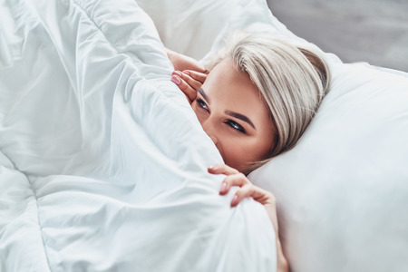 Enjoying nice morning. Attractive young woman covering half of her face with blanket and smiling while lying in bed at home