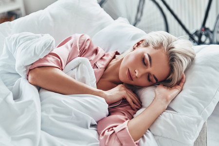 Just one more minute in bed. Top view of attractive young woman sleeping while lying in bed at home Stock Photo