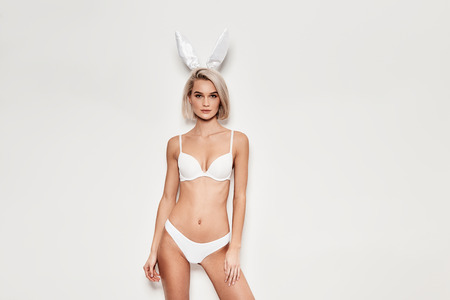 Like a bunny. Seductive young woman in lingerie looking at camera while standing against grey background