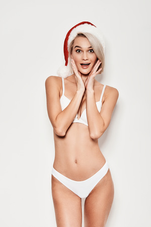 Christmas is coming! Shocked young woman in lingerie gesturing and looking at camera while standing against grey background