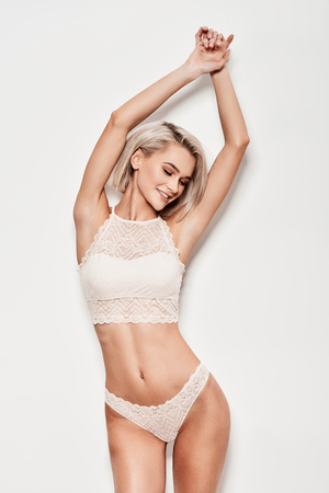 Free your femininity! Beautiful young woman in lingerie smiling while standing against grey background Stock Photo