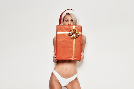 Gift for you! Surprised young woman in lingerie holding Christmas gift box and looking at camera while standing against grey background