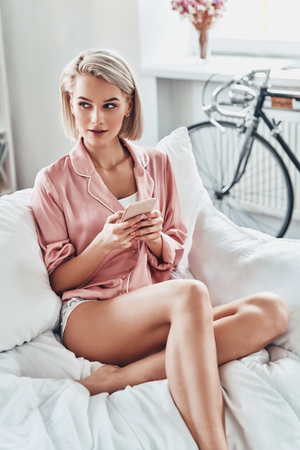 Typing another message. Attractive young woman using smart phone while sitting on bed at home