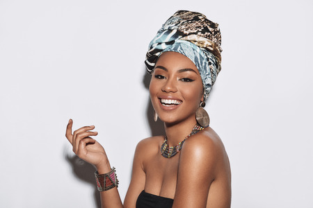 Simply happy. Attractive young African woman in turban looking at camera and smiling while standing against grey background Standard-Bild - 113301972