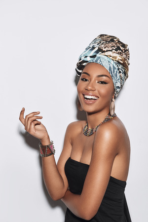 African beauty. Attractive young African woman in turban looking at camera and smiling while standing against grey background
