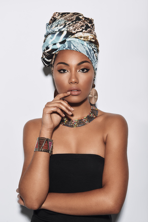 Calm and relaxed. Attractive young African woman in turban looking at camera while standing against grey background