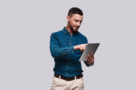 Surfing the net. Good looking young man in smart casual wear using digital tablet and smiling while standing against grey background Stock Photo
