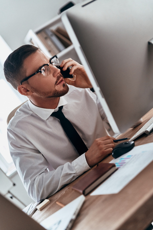 Listening to clients requirements. Serious young man in formalwear talking on the phone while sitting in the office Stock Photo