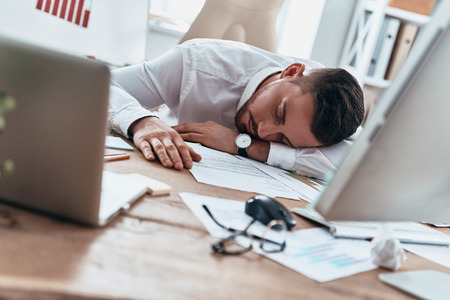 Working late hours. Tired young man in formalwear sleeping on the desk while working late
