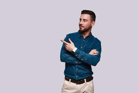 Solution is here. Handsome young man pointing copy space and smiling while standing against grey background Stock Photo
