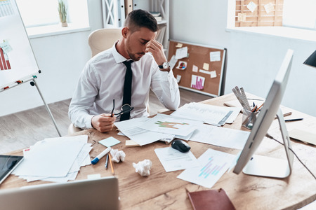 Exhaustion. Top view of tired young man in formalwear working with papers while sitting in the office Stock Photo