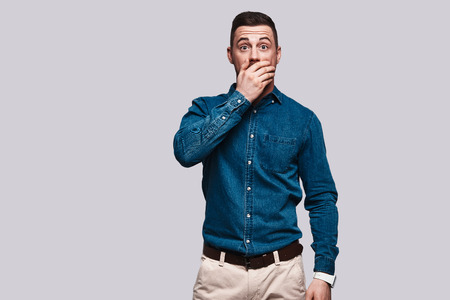 Shock. Surprised young man covering mouth with hand while standing against grey background