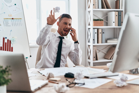 Emotional stress. Tired young man in formalwear talking on the phone and shouting while sitting in the office Stock Photo