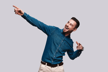 Take a look! Handsome young man pointing copy space and smiling while standing against grey background Stock Photo