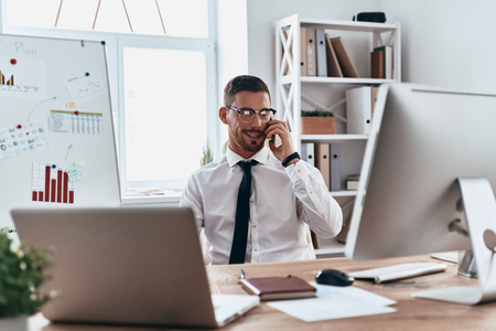 Talking with client. Handsome young man in formalwear talking on the phone and smiling while sitting in the office Stock Photo