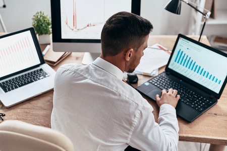 Developing new approaches. Top view of young businessman in formalwear analyzing data using computer while sitting in the office Stock Photo
