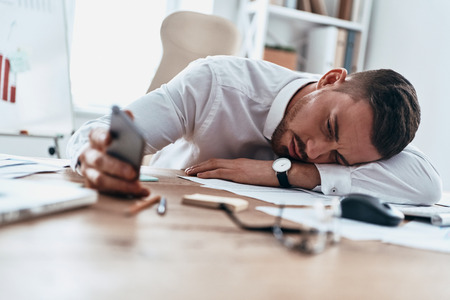 Business is tough. Tired young man in formalwear lying on the desk and using his smart phone while working late Stock Photo