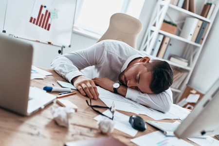 Overworked. Tired young man in formalwear sleeping on the desk while working late
