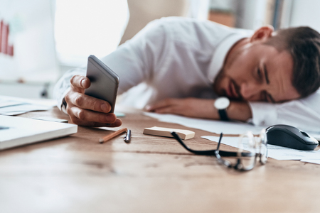 Time to get to work. Tired young man in formalwear lying on the desk while working late Stock Photo