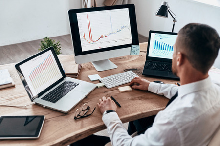 Analyzing sales pitch. Top view of young businessman in formalwear analyzing data using computer while sitting in the office Stock Photo