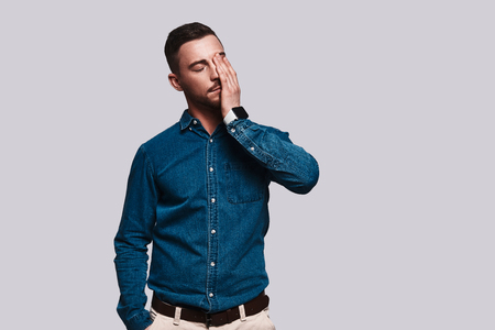 Emotional stress. Frustrated young man touching his face with hand while standing against grey background