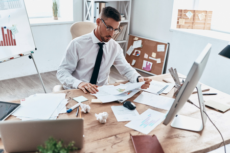 Working hard. Top view of young man in formalwear reading papers while sitting in the office Stock Photo