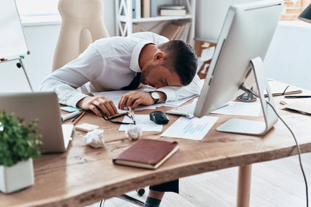 Deadline. Tired young man in formalwear sleeping on the desk while working late Stock Photo