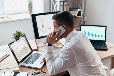 Trying to help someone. Young businessman in formalwear talking on the phone and analyzing data using computer while sitting in the office Stock Photo