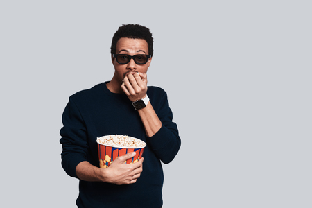 Great movie. Handsome young man in casual clothing looking at camera and eating popcorn while standing against grey background Stock Photo