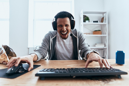 Carefree and happy. Handsome young man in casual clothing looking at camera and smiling while playing computer games at home