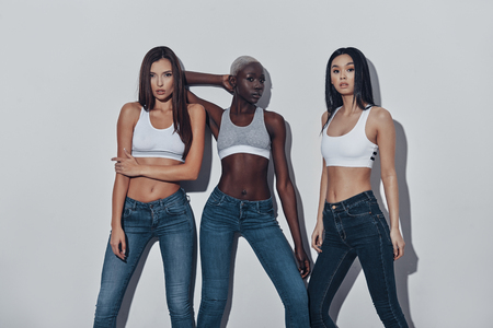 Dangerously beautiful. Three attractive young women looking at camera while standing against grey background